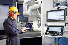 Underhållstekniker som använder den automatiska robotic handen för bärbar datordatorkontroll med CNC-maskinen i den smarta fabrik royaltyfria bilder