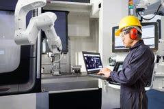 Underhållstekniker som använder den automatiska robotic handen för bärbar datordatorkontroll med CNC-maskinen i den smarta fabrik royaltyfri bild