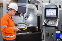 Underhållstekniker som programmerar den automatiska robotic handen med CNC royaltyfri bild