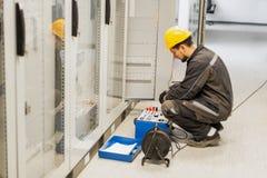 Underhållsteknikern kontrollerar systemet med equipmen för reläprovuppsättning arkivfoton