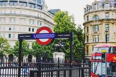 Underjordisk ingång och röd buss i Trafalgar Square, London Royaltyfri Foto
