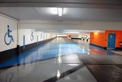 Underjordisk parkering med utrymmen som reserveras för handikappade personer arkivbild