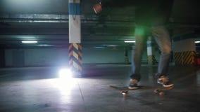 Underjordisk parkeringsplats En skateboarding för ung man Övning av ollietricket ljus lampa stock video