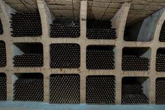 Underjordisk tappningvinkällare med vinflaskor som lagras i kuggar fotografering för bildbyråer