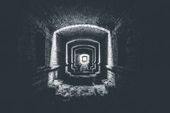 Underjordisk tunnel för förstörd tegelsten eller korridor och ljus i slutet, väg att hoppas begreppet, svartvitt foto Arkivfoton