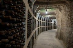 Underjordisk vinkällare med att åldras vinflaskor i kuggar arkivfoto