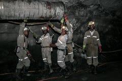 Underjordiska platinagruvarbetare som passar ett ventilationsrör royaltyfri foto