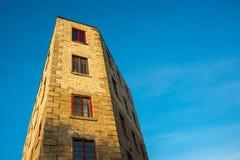 Underligt formad byggnad mot blå himmel arkivfoto