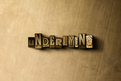 UNDERLYING - close-up of grungy vintage typeset word on metal backdrop Royalty Free Stock Images