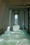 Underneath boardwalk or pier. Ocean and support structure underneath a seaside boardwalk or pier Stock Image