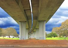Underneath a concrete road bridge. Underneath concrete road bridge with storm clouds on horizon royalty free stock photography