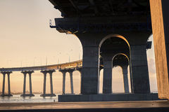 Underneath the Coronado Bridge at sunrise. San Diego, California between the bridge footers and through the arches as the rising sun casts its golden light stock image