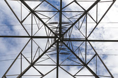 Underneath the electrical tower. Facing upwards underneath an electrical tower. Cloudy blue sky above Royalty Free Stock Image