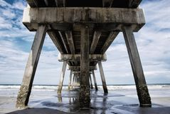 Underneath the Fishing Pier at Jacksonville Beach Florida USA. Underneath the fishing pier at Jacksonville Beach Florida with a view of the Atlantic Ocean and royalty free stock image