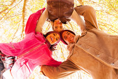 Underneath group friends. Underneath view of group of friends in a circle looking down in autumn forest stock photography