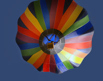 Underneath hot air balloon. Upward view on a colorful hot air balloon floating in blue sky royalty free stock photography