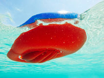 Underneath inflatable boat. Underwater view of inflatable boat bottom floating in blue waters stock photo