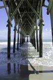 Underneath the pier. Waves breaking underneath a wooden sea pier Stock Photo