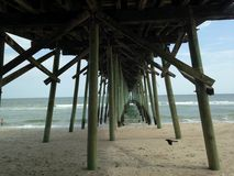 Underneath The Pier By The Sea. A perfectly timed shot that captures the beauty of the gentle crashing waves under the pier as well as a passing bird royalty free stock photography