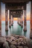 Underneath the pylons of a long jetty pier beach. Dark of underneath the pylons of a long jetty pier beach overlooking the sea at sunset or twilight at Khao Laem stock photo