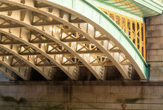 Underneath Southwark Bridge in London. Girders supporting Southwark Bridge across the Thames river in London with setting sun lighting the painted ironwork stock photos