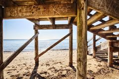 Underneath the stairs looking at the beach royalty free stock photos
