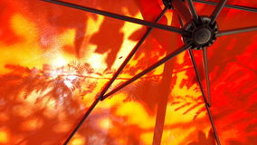 Underneath umbrella with tree shadow. Leaf shadow on outside of orange umbrella cloth. Show structure wires under stock image