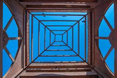 Underneath the wooden tower. View from underneath the wooden tower against a blue sky with some pigeons resting Royalty Free Stock Photo