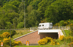 Underpass with motorhome passing on the main road. An image of a new road layout with underpass and a modern motor-home traveling east to west across Scotland Royalty Free Stock Image