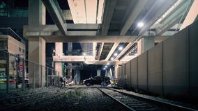 Underpass With Train Tracks In City At Night. View of city street beneath subway station with train tracks in the foreground stock footage
