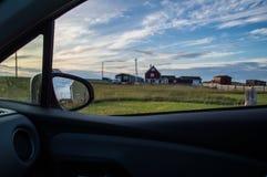 Undersök Newfoundland med uthyrnings- bil- charmiga färgrika hus och en äng på solnedgången i Bonavista Royaltyfria Bilder