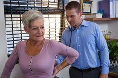 Undersöka för fysioterapeut kvinnliga patienter tillbaka Arkivfoto