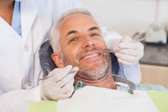 Undersöka för tandläkare patienttänder i tandläkarestolen royaltyfria foton