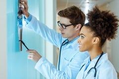 undersöka för två ungt le doktorer arkivfoto