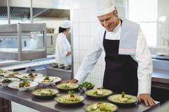 Undersökande aptitretareplattor för lycklig kock på beställningsstationen Arkivfoton