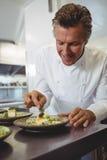 Undersökande aptitretareplattor för manlig kock på beställningsstationen Royaltyfri Fotografi