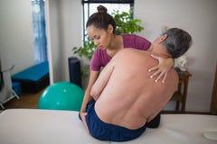 Undersökande bakdelar för ung kvinnlig terapeut av shirtless högt manligt tålmodigt sammanträde på säng royaltyfri fotografi