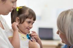 Undersökande barn för doktor med stetoskopet i klinik Mamman rymmer hennes unge arkivfoton
