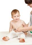 Undersökande barn för doktor på en vit bakgrund royaltyfria bilder