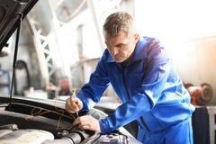 Undersökande bil för manlig mekaniker i servicemitt royaltyfri foto