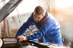 Undersökande bil för manlig mekaniker i servicemitt royaltyfri bild