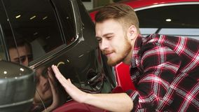 Undersökande bilmålarfärg för stilig skäggig manlig kund på en ny automatisk på återförsäljaren stock video