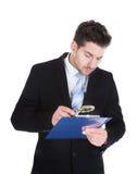 Undersökande dokument för affärsman på skrivplattan Royaltyfri Bild