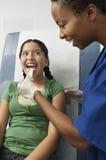 Undersökande flickas hals med tungdepressoren Arkivbilder