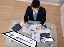 Undersökande grafer för affärsman på skrivbordet Royaltyfria Bilder