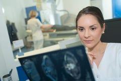 Undersökande hjärnbildläsning för kvinnlig radiolog vid mrimaskinen fotografering för bildbyråer