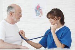 Undersökande hjärtslag för doktor av den höga mannen fotografering för bildbyråer