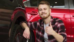 Undersökande hjul för ung man och gummihjul av en ny bil på återförsäljaren arkivfilmer