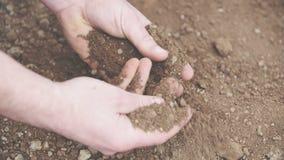 Undersökande jord för bonde i händer Fält arkivfilmer