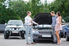 Undersökande ny bil Välj den nya automatiskn Framtida ägare av den motoriska bilen Köpande använd bil i lagret Byggnadsfamilj arkivfoto